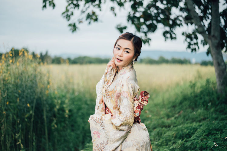 Portrait Of Young Woman Wearing Kimono Standing On Field