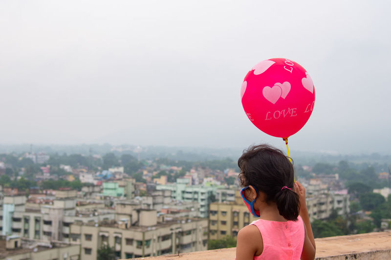 Girl with umbrella looking at city against sky