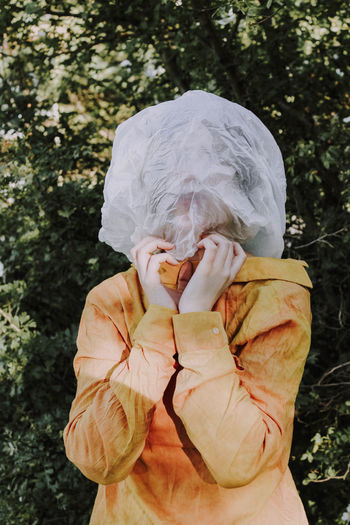 Person wearing textile over face against trees