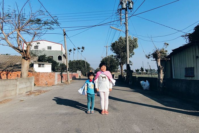 Building Exterior Architecture Built Structure Full Length Sky Tree Cable One Person Outdoors Day Power Line  Stereotypes Feminist Feminism Color-coded Casual Clothing Femininity Real People Childhood Electricity Pylon Clear Sky City People One Woman Only Adult