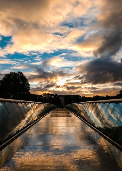 Bridge over swimming pool against sky during sunset