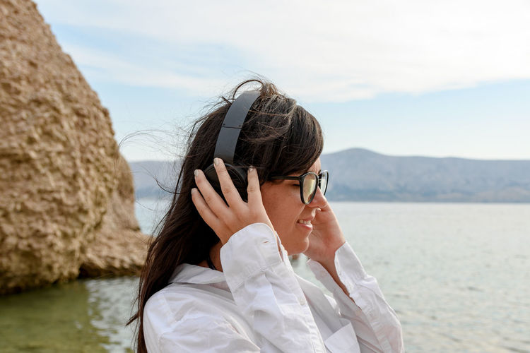 Beautiful young woman standing on beach listening to music on headphones.