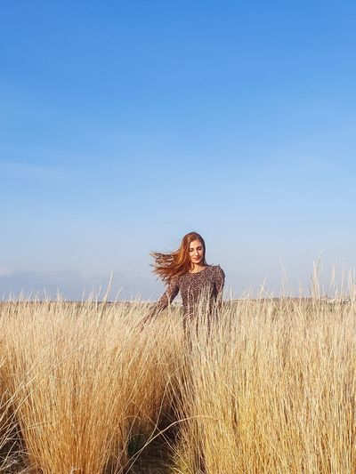 Full length of woman on grass in field against sky