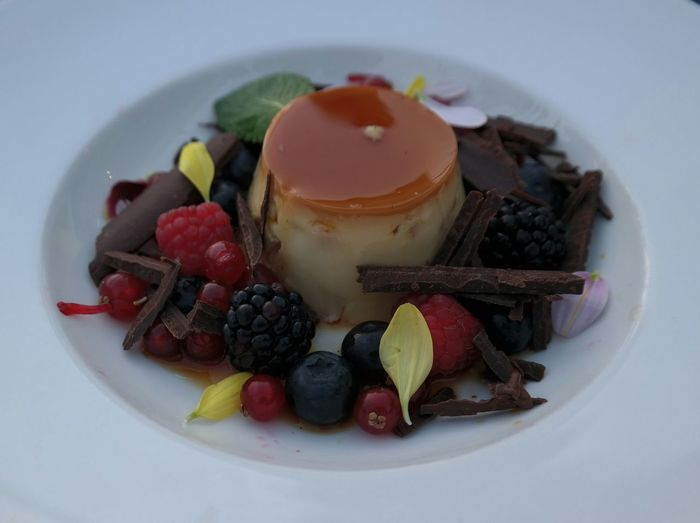 Close-Up Of Caramel Custard Served With Fresh Fruits And Chopped Chocolate Pieces In Plate