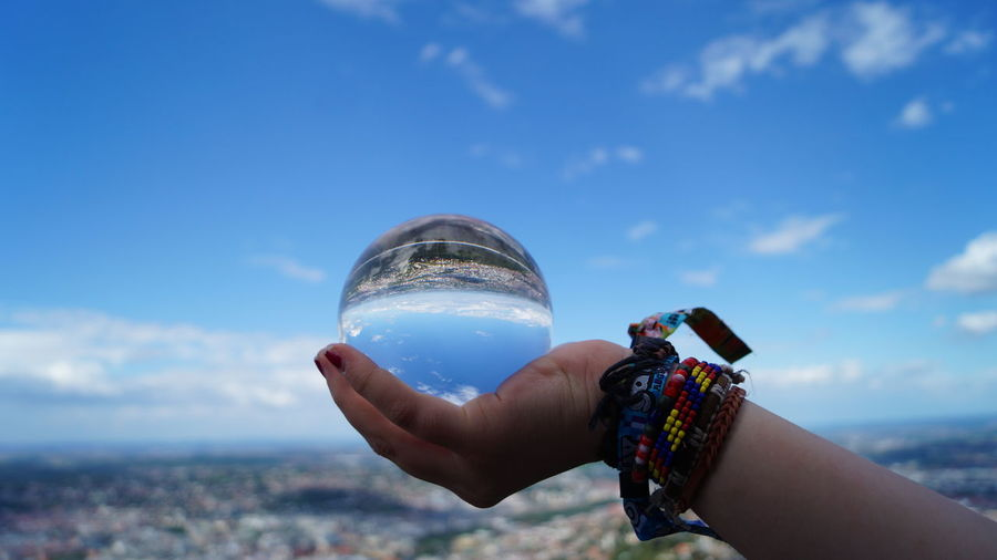 Cropped hand of woman holding crystal ball against blue sky