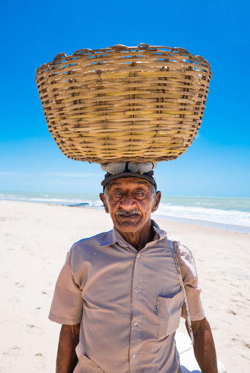 Portrait Of Vendor Standing At Beach Against Sky