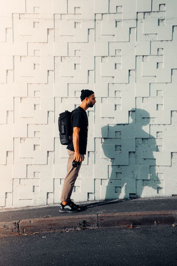 Full length of a man standing against wall