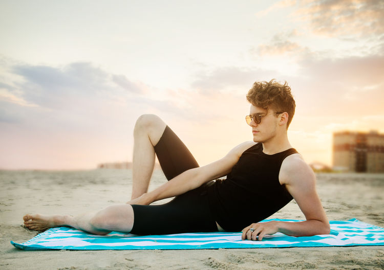 Young man relaxing at beach against sky