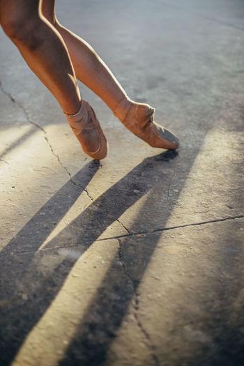 Low section of woman walking on sidewalk in city