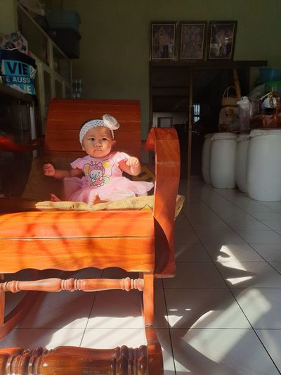 Portrait of cute girl sitting on chair