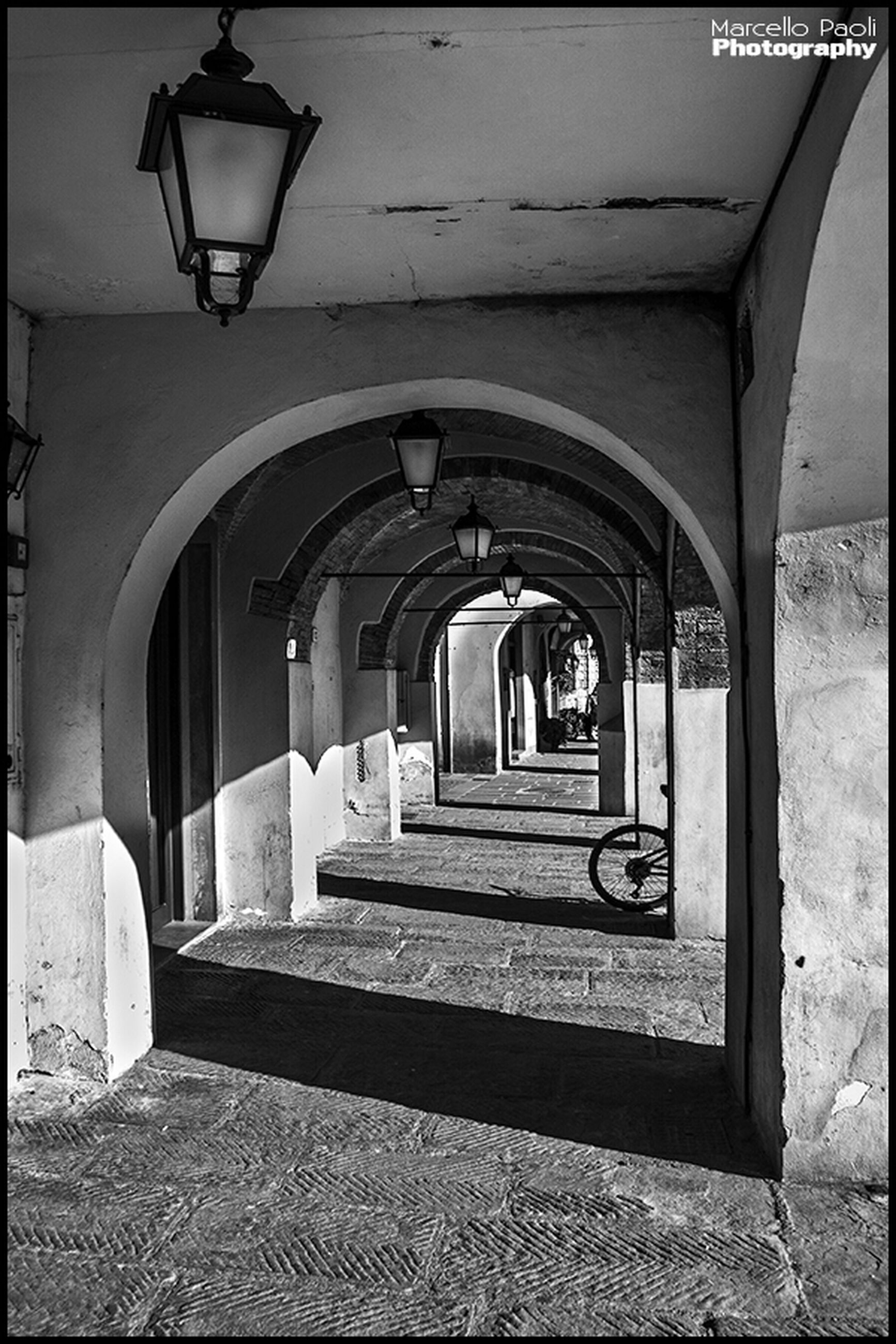 architecture, built structure, the way forward, indoors, arch, lighting equipment, corridor, empty, building exterior, ceiling, architectural column, building, diminishing perspective, absence, sunlight, steps, walkway, column, street light, railing