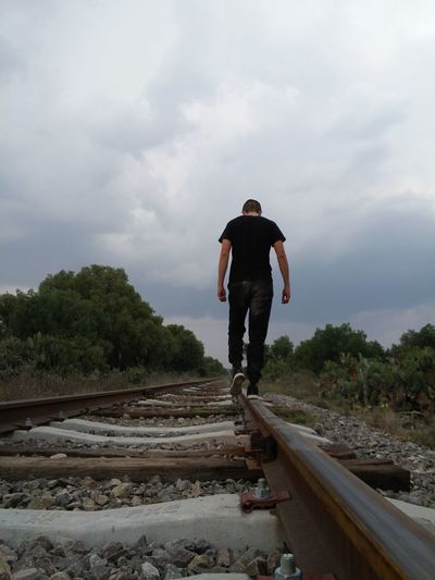 Man Walking On Railroad Track Against Sky