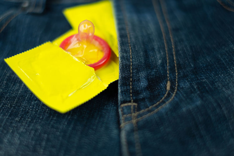 condom on jeans pocket (World AIDS Day concept), soft focus. Yellow Close-up Jeans Indoors  Textile Condom Love Safety Safe Prevention Prevent Save Protection Protect Aids Care Virus Hiv Adult Relationship Rubber Contraceptive Romance Control Jeans Denim