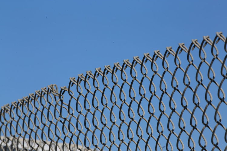 Low angle view of chainlink fence against clear blue sky