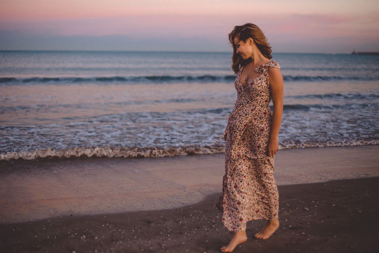 Full length of woman at beach during sunset