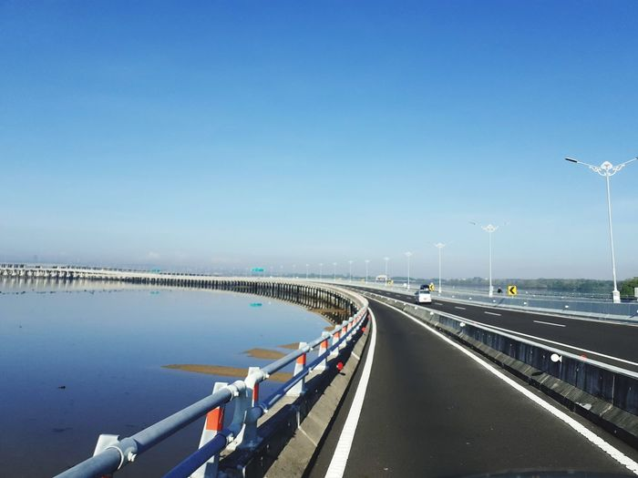 Bridge over road against clear blue sky