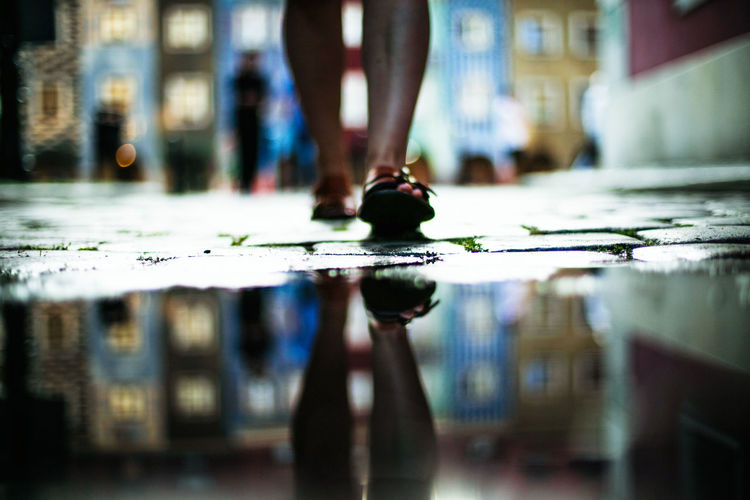 Low section of woman reflecting in puddle