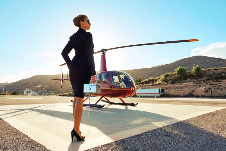 Rear View Of Businesswoman Standing By Helicopter Against Sky