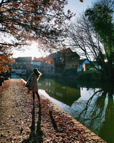 Woman standing by canal during autumn