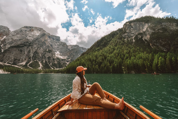Man sitting by lake against mountains