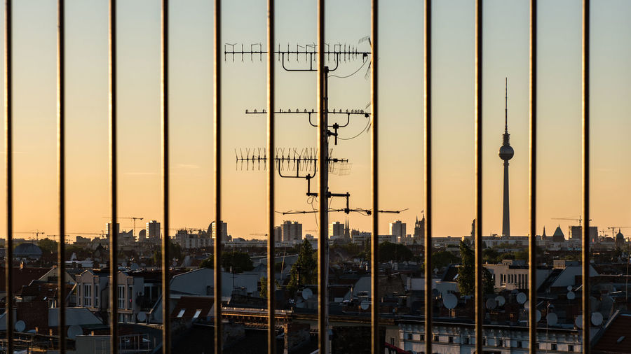 Fernsehturm and cityscape seen through railing during sunset