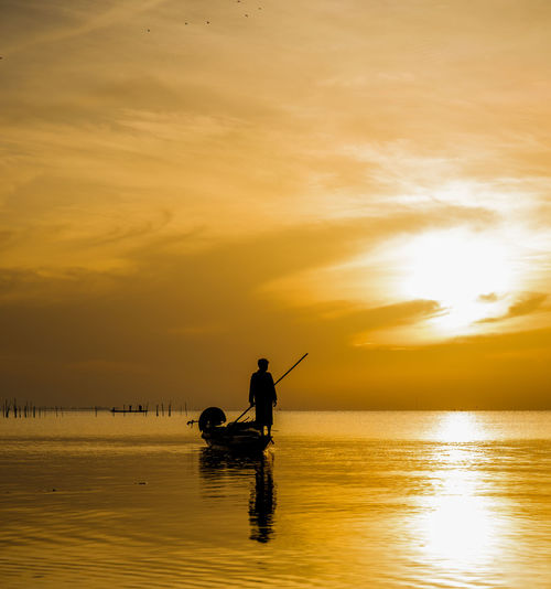 Silhouette man standing on fishing boat against sky during sunset