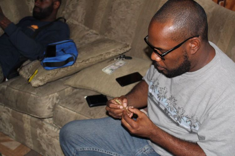 High Angle View Of Man Making Marijuana Joint On Sofa At Home