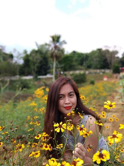 Portrait of smiling young woman with yellow flowers on field