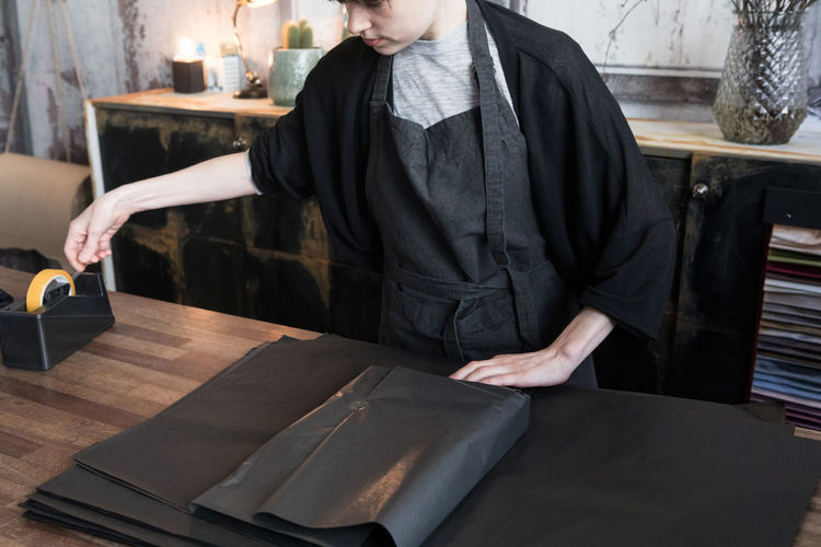 Midsection of man working on table at restaurant