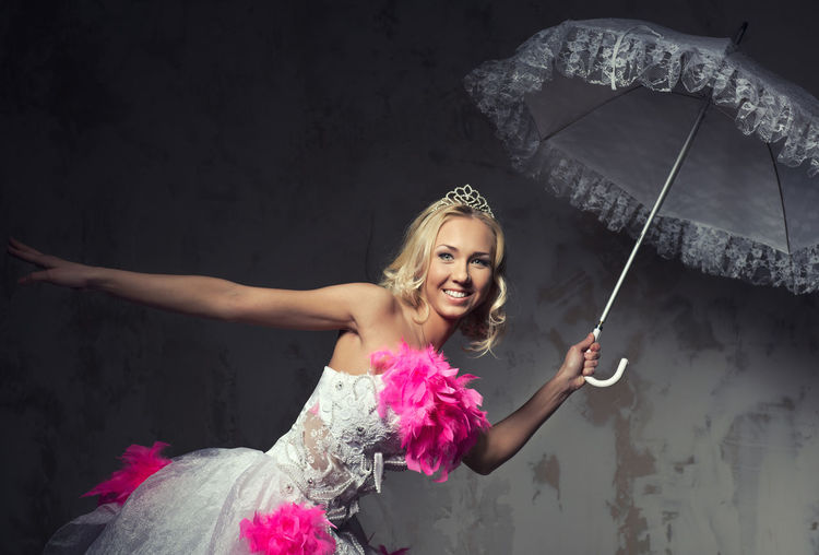 Portrait of beautiful young woman in pink and white wedding dress posing with umbrella against wall
