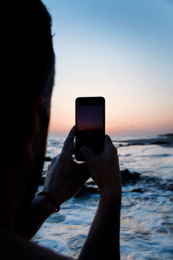Man using smart phone against sky during sunset