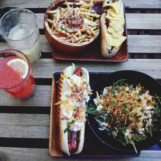 High angle view of hotdogs and salad with french fries on table