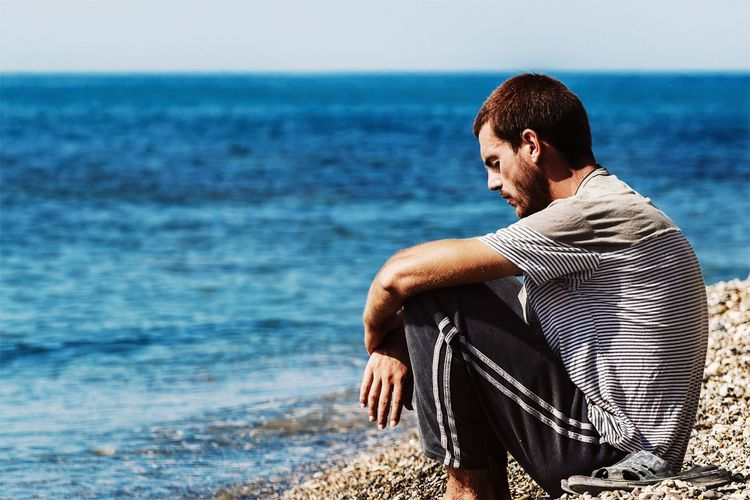 Profile View Of Man Sitting At Beach