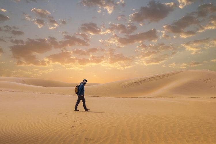 Full length of man walking on sand in desert against sky during sunset