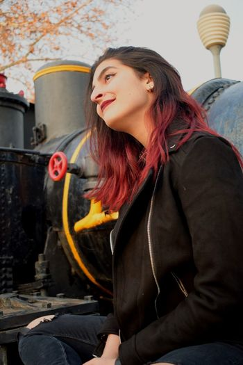 Smiling young woman sitting on steam engine