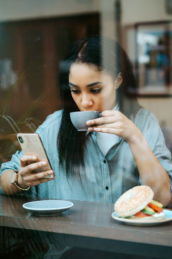 Young woman using smart phone in restaurant