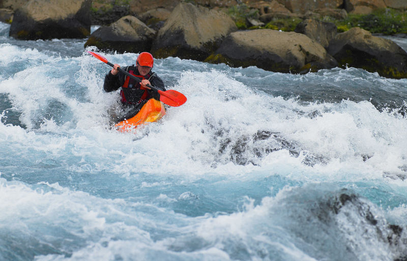 Man surfing on rock in river