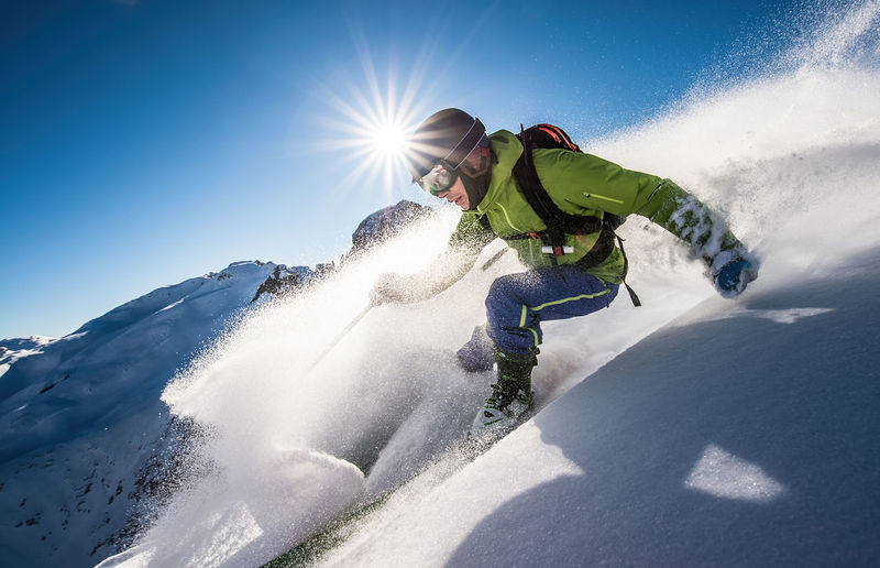 Man skiing on snowcapped mountain against sky during winter