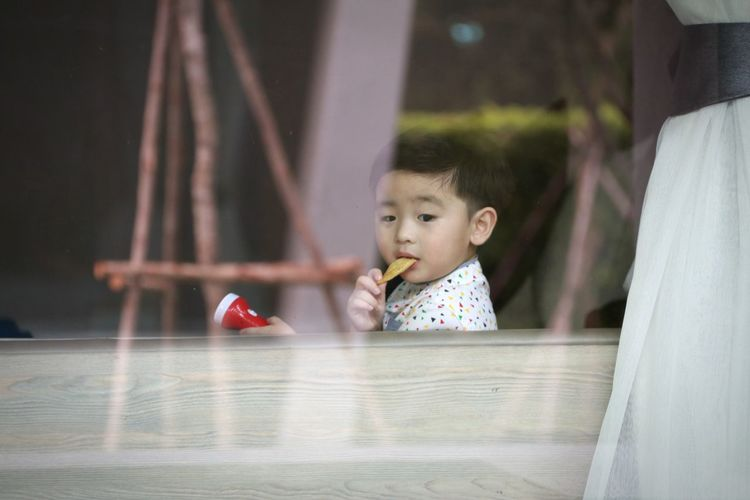 Cute boy eating food while sitting at home
