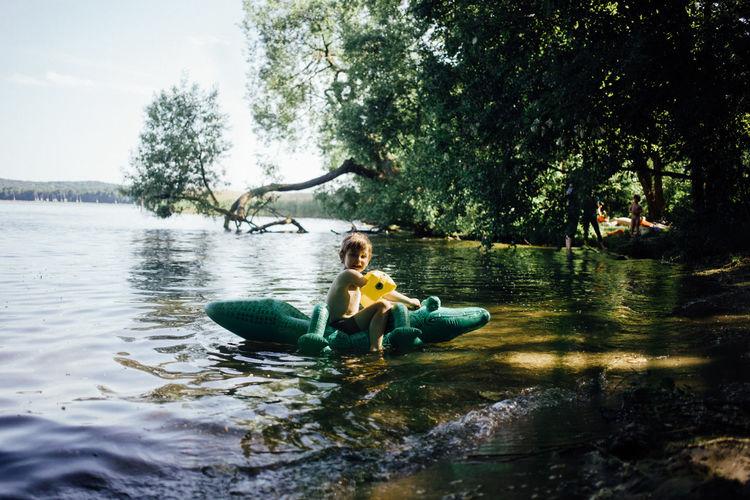 Side view of boy sitting on crocodile shape pool raft at lakeshore
