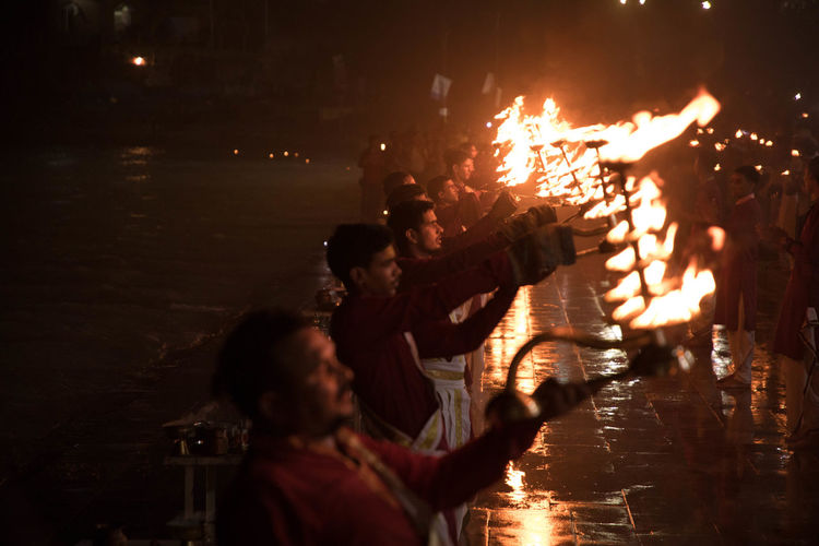 Group of people watching fire in water at night
