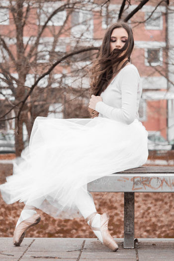Side view of young woman sitting on bench
