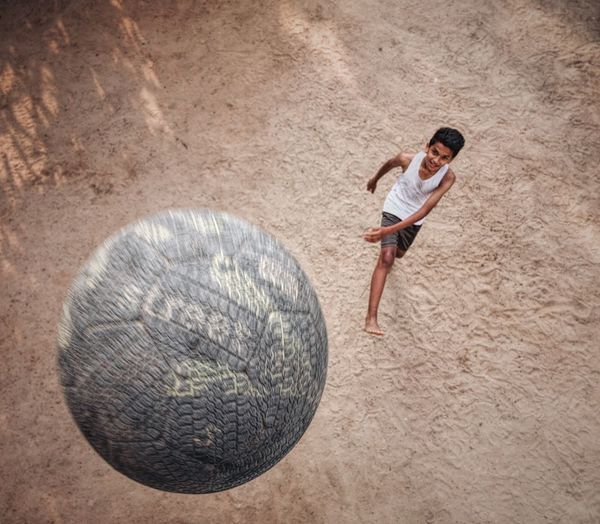 High angle view of boy playing with soccer ball