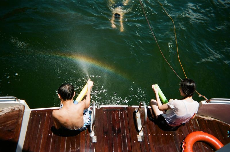 Nautical Vessel Real People Water High Angle View Leisure Activity Day Two People Shirtless Lifestyles Childhood Togetherness Outdoors Sitting Lake Nature Boys Swimming Men Adult People Rainbow Summertime Sunlight Fresh On Market 2017