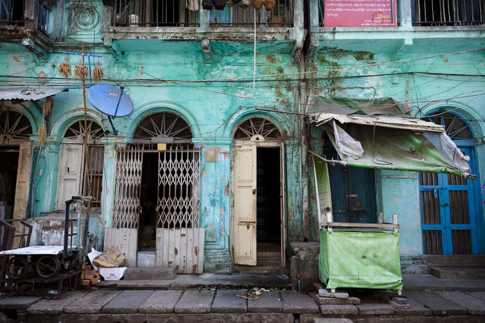 A colourful house facade in the old town of Yangon, Myanmar. Arch Arched Architecture Atmospheric Bad Condition Building Exterior Built Structure Colourful Damaged Day Deterioration Entrance Façade Façade House Obsolete Old Old Buildings Old Town Outdoors Travel Travel Destinations Wall Window Yangoon
