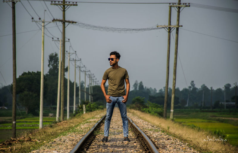 Full length of man standing on railroad track