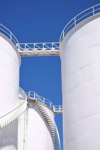 Low angle view of white storage fuel tanks with curve metal stairs against blue clear sky in sunny day, vertical frame Bright Plant White Vertical Frame Low Angle View Cylinder Clear Sky Blue Business Finance And Industry Factory Sky Architecture Petrochemical Plant Chemical Plant Refinery Oil Refinery Fuel Storage Tank Storage Tank Oil Industry Cable-stayed Bridge Gas Residential Structure Steps And Staircases Spiral Staircase Stairs Steps