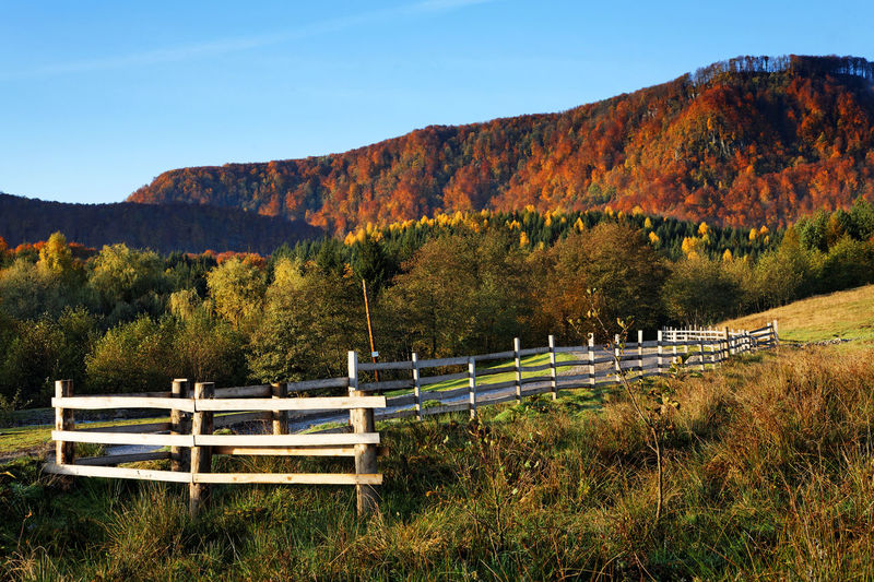 Scenic View Of Wooden Fence Against Mountains In Autumn