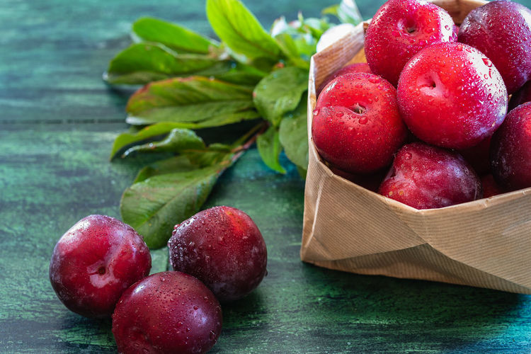 Red plums in a basket and scattered on a rustic base Dessert Plant Red Rustic Close-up Fall Food Freshness Fruit Healthy Eating Ingredient Juicy Fruit Leaf Organic Organic Food Plant Part Plum Purple Raw Food Red Ripe Still Life Summer Sweet Food Wooden Texture