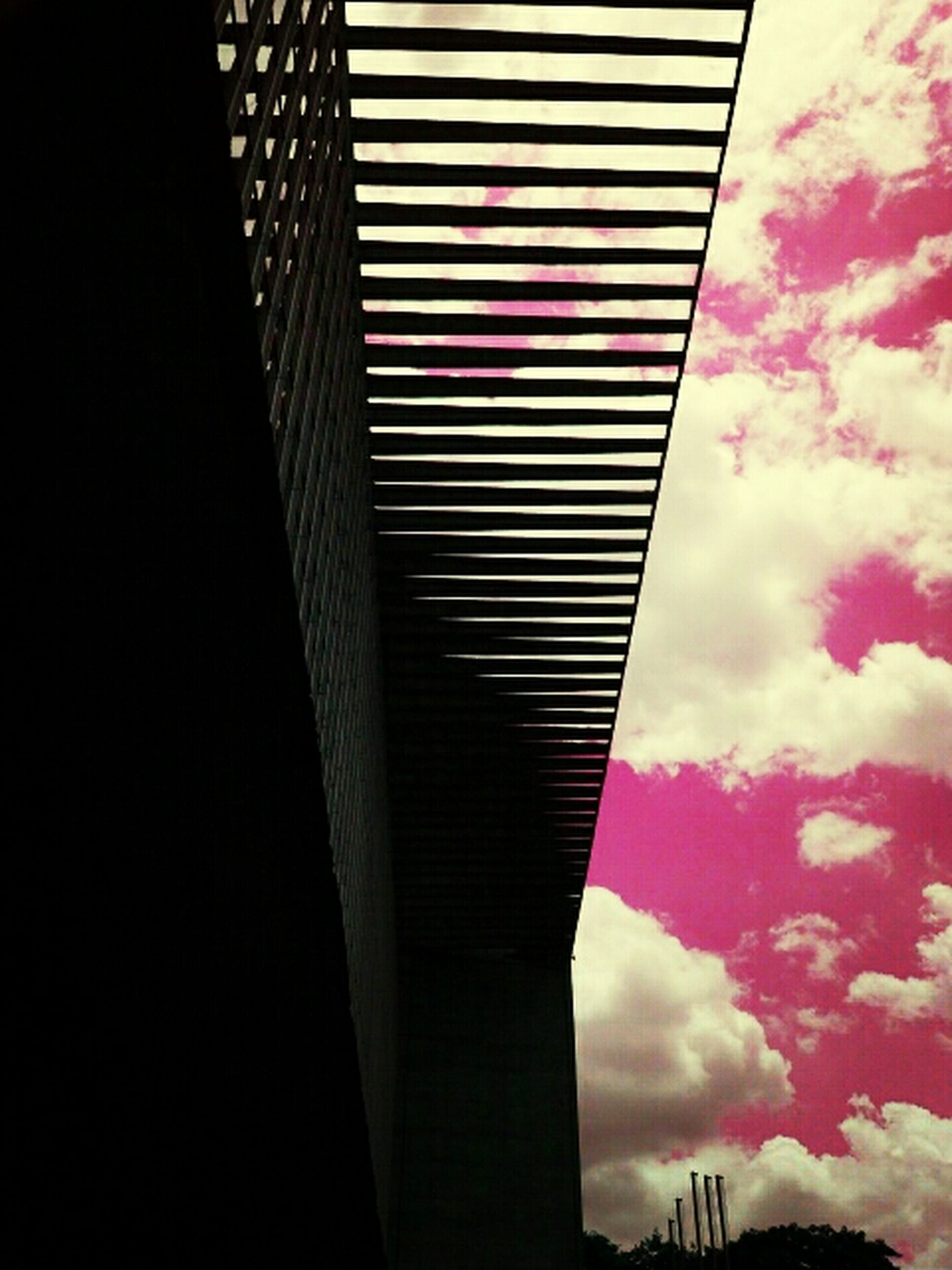 low angle view, sky, architecture, built structure, cloud - sky, building exterior, cloudy, cloud, city, flag, overcast, outdoors, no people, day, building, tall - high, modern, red, tower, weather